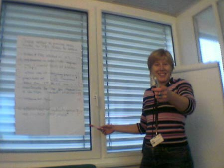 Stephanie waving pens at her colleagues while facilitating a decision analysis exercise.